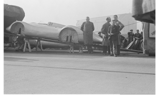 Прикрепленное изображение: Auto Union International body on a ramp. Behind the ramp is the Auto Union Type C Streamliner used in the record attempt. The cars are outside of the Zeppelinhalle hangar.png
